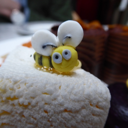 Cheeky Honey Bee sitting on honey sponge, honey and jasmine centre, white velvet crust